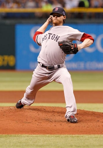 Oct 7, 2013; St. Petersburg, FL, USA; Boston Red Sox starting pitcher Clay Buchholz (11) throws a pitch against the Tampa Bay Rays during the first inning of game three of the American League divisional series at Tropicana Field. Mandatory Credit: Kim Klement-USA TODAY Sports