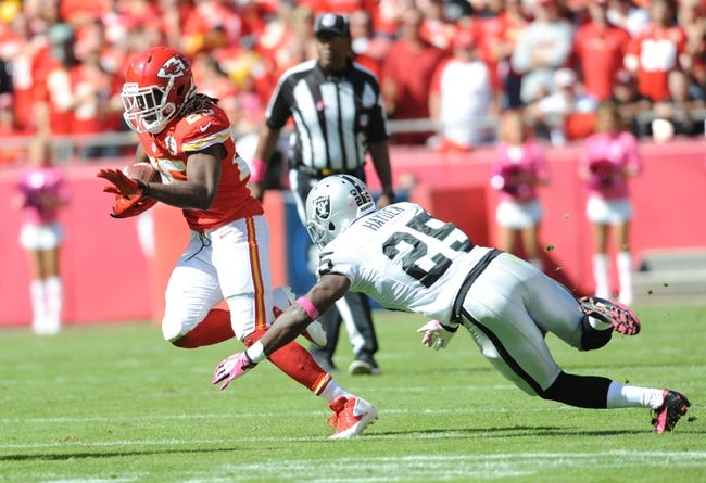 Oct 13, 2013; Kansas City, MO, USA; Kansas City Chiefs running back Jamaal Charles (25) runs the ball as Oakland Raiders cornerback D.J. Hayden (25) attempts the tackle during the first half at Arrowhead Stadium. The Chiefs won 24-7. Mandatory Credit: Denny Medley-USA TODAY Sports