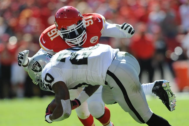 Oct 13, 2013; Kansas City, MO, USA; Oakland Raiders running back Darren McFadden (20) is tackled by Kansas City Chiefs outside linebacker Tamba Hali (91) during the first half at Arrowhead Stadium. The Chiefs won 24-7. Mandatory Credit: Denny Medley-USA TODAY Sports