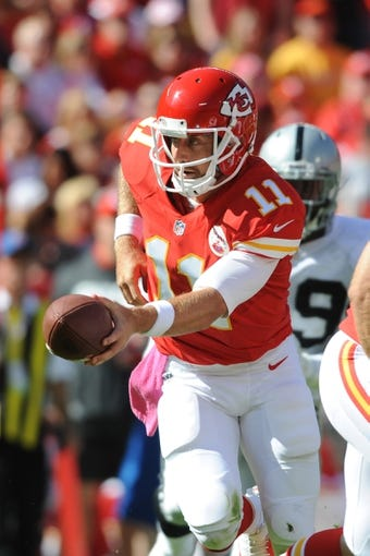Oct 13, 2013; Kansas City, MO, USA; Kansas City Chiefs quarterback Alex Smith (11) hands off the ball during the first half of the game against the Oakland Raiders at Arrowhead Stadium. The Chiefs won 24-7. Mandatory Credit: Denny Medley-USA TODAY Sports