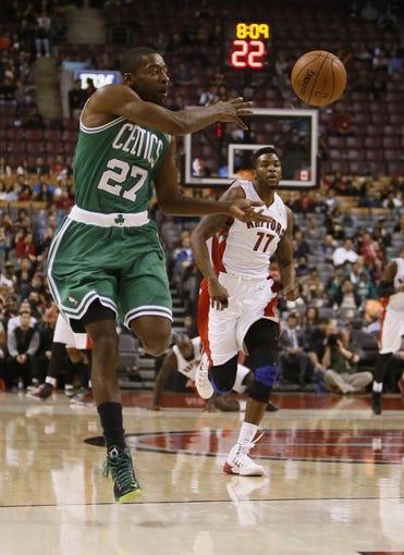 Oct 16, 2013; Toronto, Ontario, CAN; Boston Celtics guard Jordan Crawford (27) passes the ball as Toronto Raptors guard Julyan Stone (77) chases during the second half at Air Canada Centre. Toronto defeated Boston 99-97. Mandatory Credit: John E. Sokolowski-USA TODAY Sports