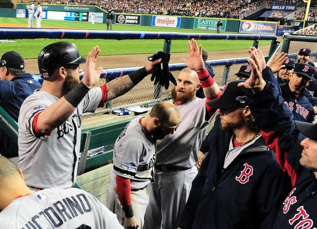 Oct 16, 2013; Detroit, MI, USA; Boston Red Sox first baseman Mike Napoli (12) celebrates with teammates after scoring against the Detroit Tigers during the sixth inning in game four of the American League Championship Series baseball game at Comerica Park. Mandatory Credit: Andrew Weber-USA TODAY Sports