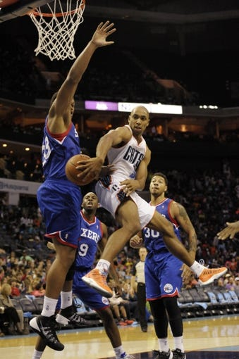 Oct 17, 2013; Charlotte, NC, USA; Charlotte Bobcats guard Gerald Henderson (9) passes the ball as he is defended by Philadelphia 76ers center Daniel Orton (33) during the pre season game at Time Warner Cable Arena. Bobcats win 11-84.  Mandatory Credit: Sam Sharpe-USA TODAY Sports
