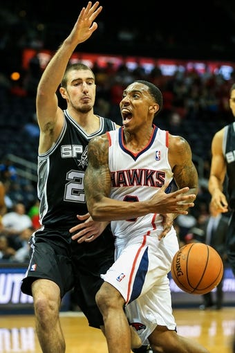 Oct 17, 2013; Atlanta, GA, USA; Atlanta Hawks point guard Jeff Teague (0) is fouled on the way to the basket by San Antonio Spurs point guard Nando de Colo (25) in the first half at Philips Arena. Mandatory Credit: Daniel Shirey-USA TODAY Sports