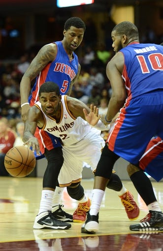 Oct 17, 2013; Cleveland, OH, USA; Cleveland Cavaliers point guard Kyrie Irving (2) dribbles through Detroit Pistons guard Kentavious Caldwell-Pope (5) and center Greg Monroe (10) during the game at Quicken Loans Arena. Mandatory Credit: Eric P. Mull-USA TODAY Sports