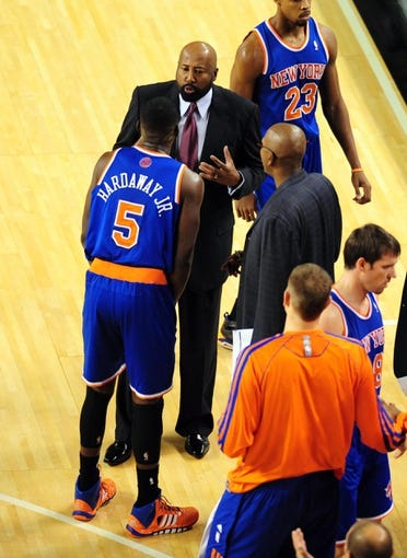 Oct 17, 2013; Baltimore, MD, USA; New York Knicks head coach Mike Woodson (center) talks to guard Tim Hardaway Jr. (5) in the third quarter against the Washington Wizards at Baltimore Arena. Mandatory Credit: Evan Habeeb-USA TODAY Sports
