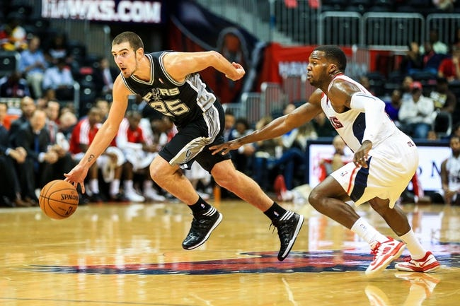 Oct 17, 2013; Atlanta, GA, USA; San Antonio Spurs point guard Nando de Colo (25) dribbles past Atlanta Hawks point guard Shelvin Mack (8) in the second half at Philips Arena. The Spurs won 106-104. Mandatory Credit: Daniel Shirey-USA TODAY Sports