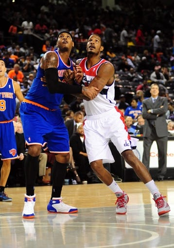 Oct 17, 2013; Baltimore, MD, USA; New York Knicks forward Carmelo Anthony (7) fights for a rebound with Washington Wizards forward Trevor Ariza (1) at Baltimore Arena. Mandatory Credit: Evan Habeeb-USA TODAY Sports