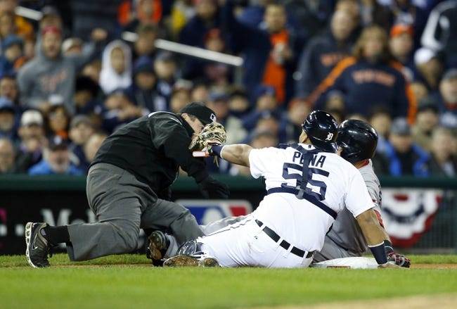 Oct 17, 2013; Detroit, MI, USA; Detroit Tigers catcher Brayan Pena (55) cannot tag Boston Red Sox third baseman Will Middlebrooks (16) because the umpire is in between him and the runner during the ninth inning in game five of the American League Championship Series baseball game at Comerica Park. Mandatory Credit: Rick Osentoski-USA TODAY Sports