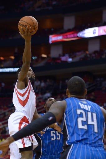 Oct 16, 2013; Houston, TX, USA; Houston Rockets point guard Aaron Brooks (0) shoots over Orlando Magic small forward Romero Osby (24) during the second half at Toyota Center. The Rockets won 108-104. Mandatory Credit: Thomas Campbell-USA TODAY Sports