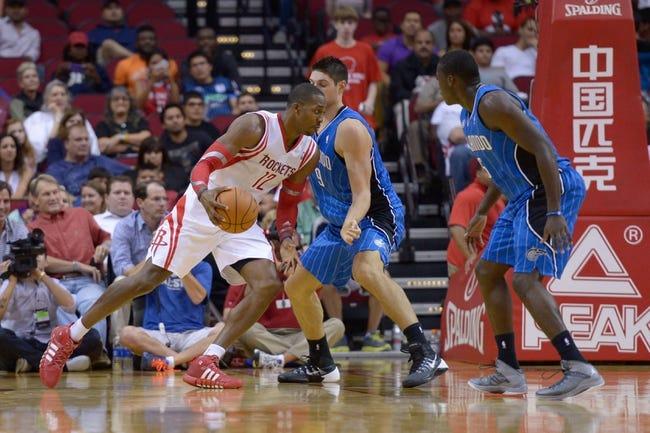 Oct 16, 2013; Houston, TX, USA; Houston Rockets center Dwight Howard (12) drives against Orlando Magic center Nikola Vucevic (9) during the first half at Toyota Center. Mandatory Credit: Thomas Campbell-USA TODAY Sports