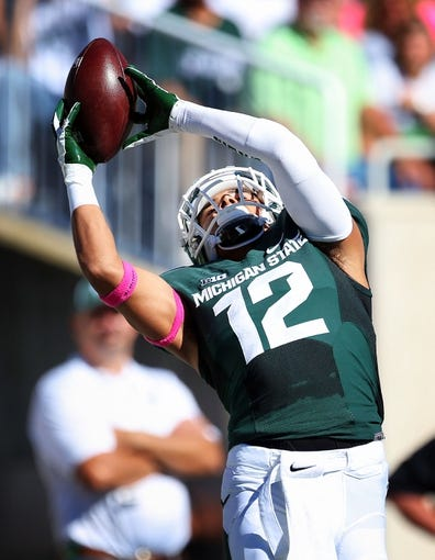 Oct 12, 2013; East Lansing, MI, USA; Michigan State Spartans running back R.J. Shelton (12) makes a fair catch of Indiana Hoosiers kick off during the second half in a game at Spartan Stadium. MSU won 42-28. Mandatory Credit: Mike Carter-USA TODAY Sports
