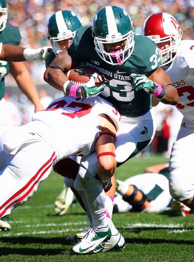 Oct 12, 2013; East Lansing, MI, USA; Michigan State Spartans running back Jeremy Langford (33) is tackled by Indiana Hoosiers safety Mark Murphy (37) during the first half in a game at Spartan Stadium. Mandatory Credit: Mike Carter-USA TODAY Sports