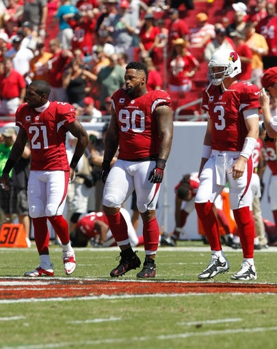Sep 29, 2013; Tampa, FL, USA; Captains of the Arizona Cardinals,  cornerback Patrick Peterson (21), defensive end Darnell Dockett (90) and quarterback Carson Palmer (3) walk to the field against the Tampa Bay Buccaneers during the first quarter at Raymond James Stadium. Mandatory Credit: Kim Klement-USA TODAY Sports