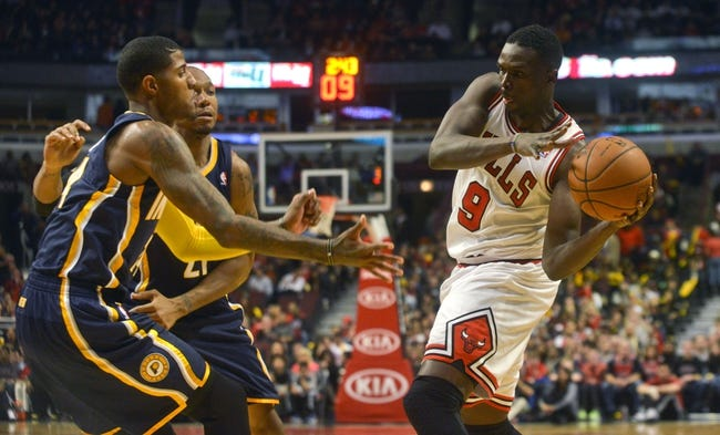Oct 18, 2013; Chicago, IL, USA; Chicago Bulls forward Luol Deng passes against the Indiana Pacers guard Paul George and forward David West at the United Center. Mandatory Credit: Matt Marton-USA TODAY Sports