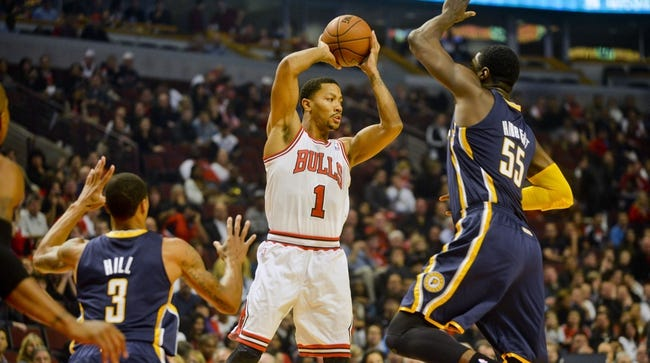 Oct 18, 2013; Chicago, IL, USA; Chicago Bulls guard Derrick Rose passes against the Indian Pacers George Hill and Roy Hibbert at the United Center. Mandatory Credit: Matt Marton-USA TODAY Sports