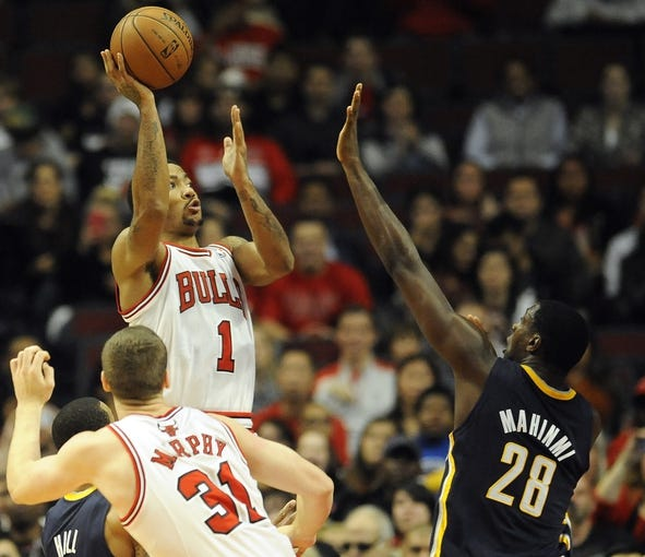 Oct 18, 2013; Chicago, IL, USA; Chicago Bulls guard Derrick Rose shoots against the Indiana Pacers center Ian Mahinmi at the United Center. Mandatory Credit: Matt Marton-USA TODAY Sports