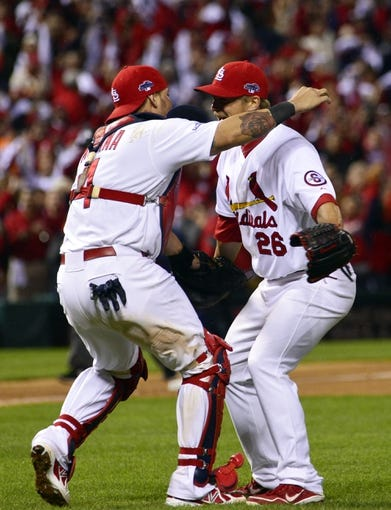 Oct 18, 2013; St. Louis, MO, USA; St. Louis Cardinals relief pitcher Trevor Rosenthal (right) celebrates with catcher Yadier Molina (left) after game six of the National League Championship Series baseball game against the Los Angeles Dodgers at Busch Stadium. Mandatory Credit: Scott Rovak-USA TODAY Sports