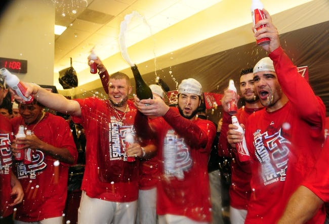 Oct 18, 2013; St. Louis, MO, USA; St. Louis Cardinals players Matt Adams (left), Tony Cruz (middle) and Jaime Garcia celebrate in the clubhouse after game six of the National League Championship Series baseball game against the Los Angeles Dodgers at Busch Stadium. Mandatory Credit: Jeff Curry-USA TODAY Sports