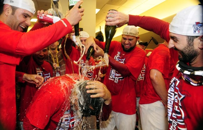 Oct 18, 2013; St. Louis, MO, USA; St. Louis Cardinals center fielder Jon Jay (bottom) is doused by teammates in the clubhouse after game six of the National League Championship Series baseball game against the Los Angeles Dodgers at Busch Stadium. Mandatory Credit: Jeff Curry-USA TODAY Sports