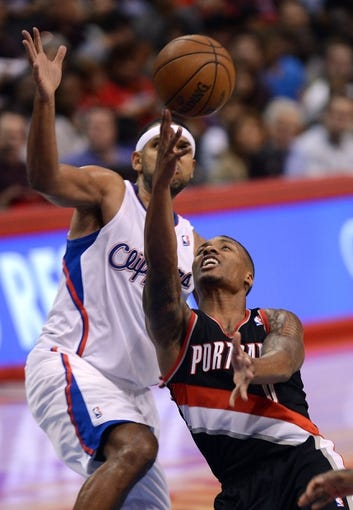 Oct 18, 2013; Los Angeles, CA, USA; Portland Trail Blazers point guard Damian Lillard (0) takes a shot as Los Angeles Clippers shooting guard Jared Dudley (9) defends in the second half of the game at the Staples Center. Mandatory Credit: Jayne Kamin-Oncea-USA TODAY Sports