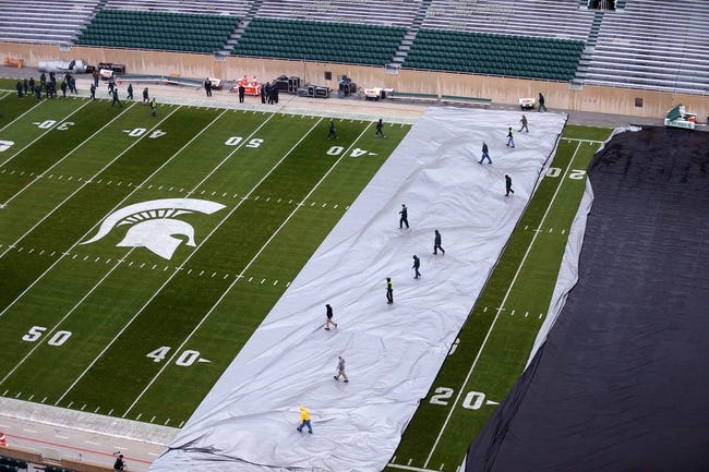 Oct 19, 2013; East Lansing, MI, USA; General view of workers removing tarps from the field prior to a game between the Michigan State Spartans and the Indiana Hoosiers at Spartan Stadium. Mandatory Credit: Mike Carter-USA TODAY Sports