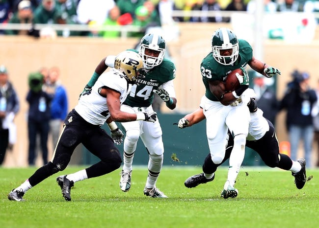 Oct 19, 2013; East Lansing, MI, USA; Michigan State Spartans running back Jeremy Langford (33) runs the ball against Purdue Boilermakers defensive back Frankie Williams (24) during the 1st quarter at Spartan Stadium. Mandatory Credit: Mike Carter-USA TODAY Sports