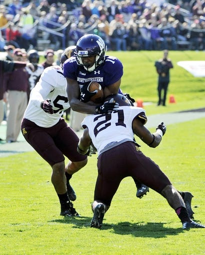 Oct 19, 2013; Evanston, IL, USA;  Northwestern Wildcats wide receiver Christian Jones (14) is tackled by Minnesota Golden Gophers defensive back Brock Vereen (21) and linebacker Aaron Hill (57) during the first quarter at Ryan Field. Mandatory Credit: David Banks-USA TODAY Sports