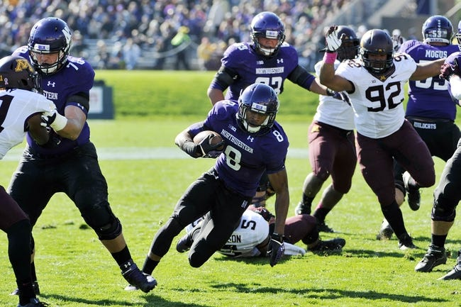 Oct 19, 2013; Evanston, IL, USA; Northwestern Wildcats running back Stephen Buckley (8) runs against the Minnesota Golden Gophers during the first quarter at Ryan Field. Mandatory Credit: David Banks-USA TODAY Sports
