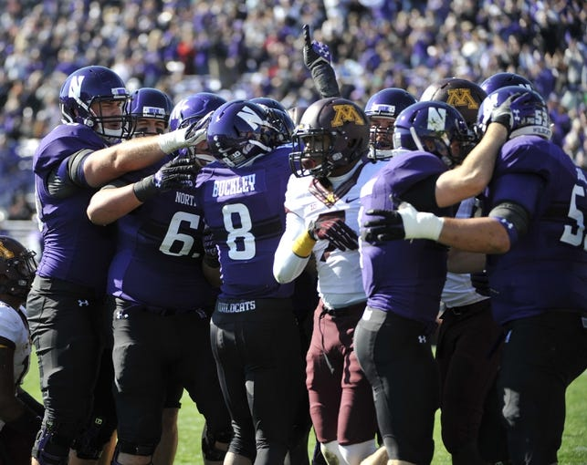 Oct 19, 2013; Evanston, IL, USA; Northwestern Wildcats running back Stephen Buckley (8)  celebrates after scoring a touchdown against the Minnesota Golden Gophers during the first quarter at Ryan Field. Mandatory Credit: David Banks-USA TODAY Sports