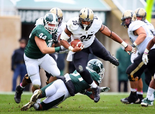 Oct 19, 2013; East Lansing, MI, USA; Purdue Boilermakers running back Brandon Cottom (25) is up ended by Michigan State Spartans cornerback Darqueze Dennard (31) during the 1st  half at Spartan Stadium. Mandatory Credit: Mike Carter-USA TODAY Sports
