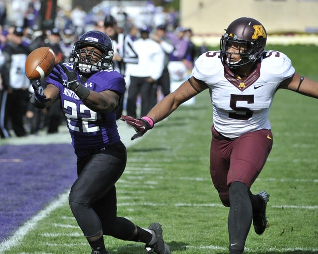 Oct 19, 2013; Evanston, IL, USA; Northwestern Wildcats running back Treyvon Green (22) is defended by Minnesota Golden Gophers linebacker Damien Wilson (5) during the second half at Ryan Field.  The Minnesota Golden Gophers defeated the Northwestern Wildcats 20-17. Mandatory Credit: David Banks-USA TODAY Sports