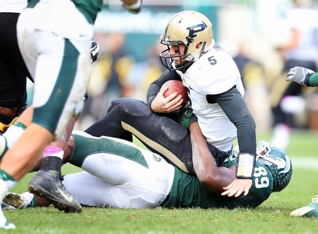 Oct 19, 2013; East Lansing, MI, USA; Purdue Boilermakers quarterback Danny Etling (5) is sacked by Michigan State Spartans defensive end Shilique Calhoun (89) during the 2nd half at Spartan Stadium. MSU won 14-0. Mandatory Credit: Mike Carter-USA TODAY Sports