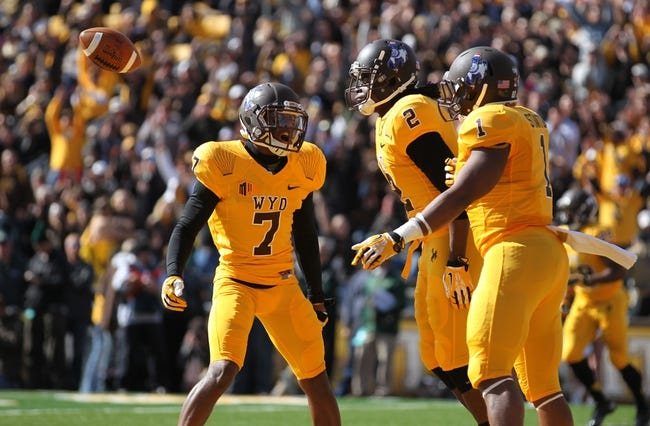 Oct 19, 2013; Laramie, WY, USA; Wyoming Cowboys safety Marqueston Huff (2) celebrates an interception with teammates Chad Reese (7) and Jordan Stanton (1) against the Colorado State Rams during the first quarter at War Memorial Stadium. Mandatory Credit: Troy Babbitt-USA TODAY Sports