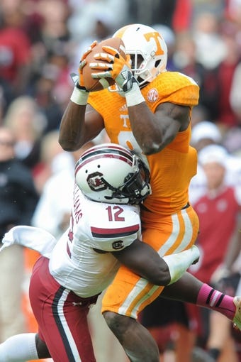 Oct 19, 2013; Knoxville, TN, USA; Tennessee Volunteers wide receiver Marquez North (8) catches a pass while being defended by South Carolina Gamecocks safety Brison Williams (12) during the second half at Neyland Stadium. Tennessee won 23 to 21.  Mandatory Credit: Randy Sartin-USA TODAY Sports