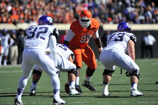 Oct 19, 2013; Stillwater, OK, USA; Oklahoma State Cowboys defensive tackle Calvin Barnett (99) gets set on defense against the Texas Christian Horned Frogs during the first half at Boone Pickens Stadium. Oklahoma State won 24-10. Mandatory Credit: Peter G. Aiken-USA TODAY Sports