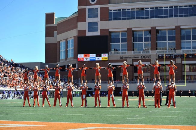 Oct 19, 2013; Stillwater, OK, USA; Members of the Oklahoma State Cowboys cheer team perform during a game against the Texas Christian Horned Frogs at Boone Pickens Stadium. Oklahoma State won 24-10. Mandatory Credit: Peter G. Aiken-USA TODAY Sports