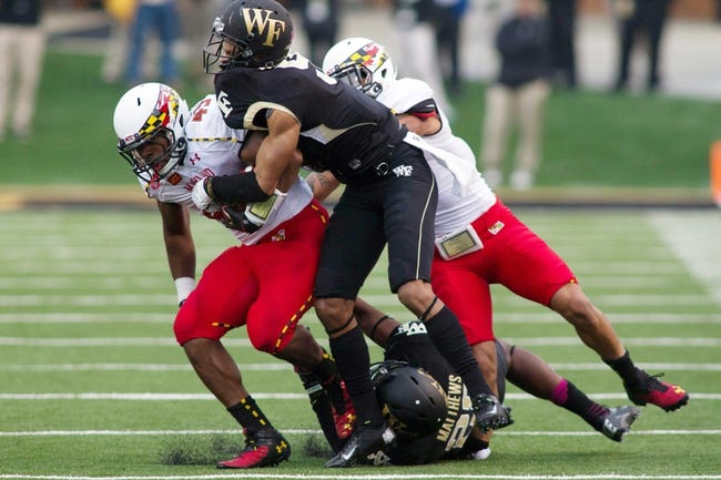 Oct 19, 2013; Winston-Salem, NC, USA;  Maryland Terrapins running back Brandon Ross (45) gets tackled by Wake Forest Demon Deacons cornerback Kevin Johnson (9) during the second quarter at BB&T Field. Maryland Terrapins wide receiver Deon Long (right) was injured on the play.  Mandatory Credit: Jeremy Brevard-USA TODAY Sports