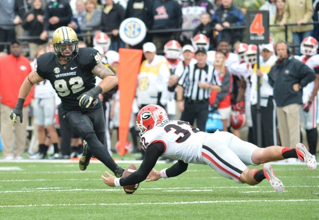 Oct 19, 2013; Nashville, TN, USA; Vanderbilt Commodores defensive end Kyle Woestmann (92) chases a loose ball as Georgia Bulldogs punter Collin Barber (32) falls on the football during the second half at Vanderbilt Stadium. The Commodores beat the Bulldogs 31-27. Mandatory Credit: Don McPeak-USA TODAY Sports