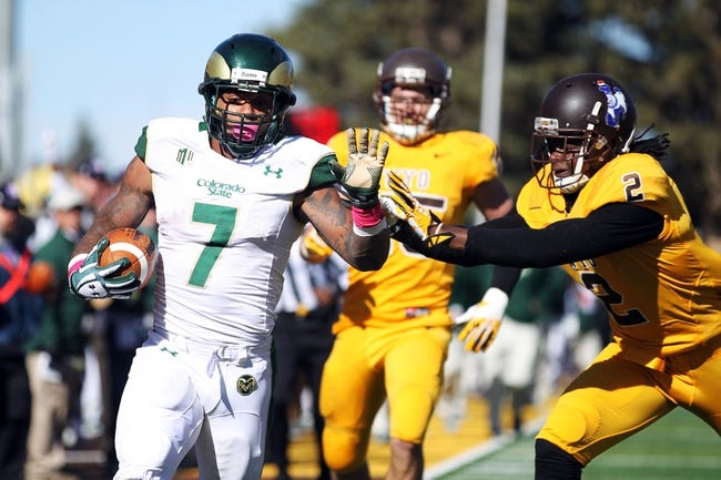 Oct 19, 2013; Laramie, WY, USA; Colorado State Rams running back Donnell Alexander (7) makes a catch and runs for a touchdown against Wyoming Cowboys safety Marqueston Huff (2) during the third quarter at War Memorial Stadium.  The Rams defeated the Cowboys 52-22.   Mandatory Credit: Troy Babbitt-USA TODAY Sports