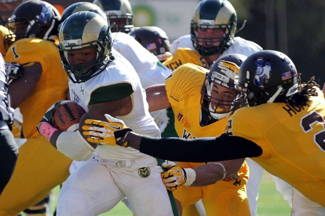 Oct 19, 2013; Laramie, WY, USA; Colorado State Rams running back Kapri Bibbs (5) runs for a touchdown against Wyoming Cowboys safety Marqueston Huff (2) during the fourth quarter at War Memorial Stadium.  The Rams defeated the Cowboys 52-22.   Mandatory Credit: Troy Babbitt-USA TODAY Sports
