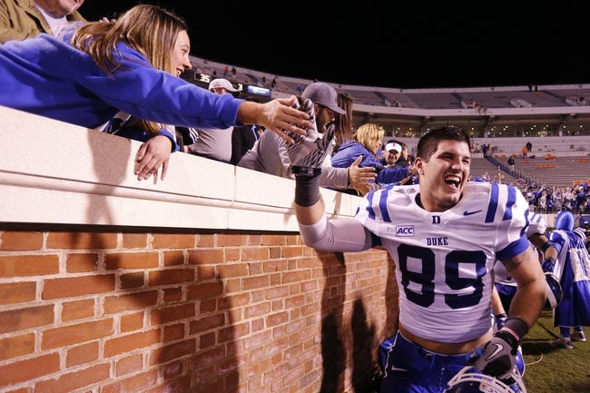 Oct 19, 2013; Charlottesville, VA, USA;  Duke Blue Devils tight end Braxton Deaver (89) celebrates with fans in the stands after their game against the Virginia Cavaliers at Scott Stadium. The Blue Devils won 35-22. Mandatory Credit: Geoff Burke-USA TODAY Sports