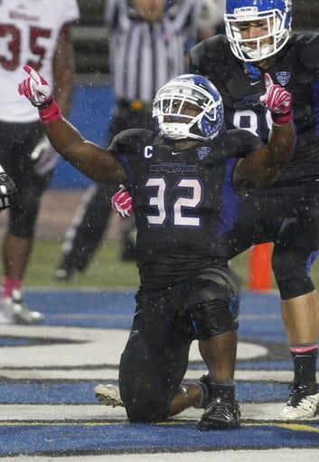 Oct 19, 2013; Buffalo, NY, USA; Buffalo Bulls running back Branden Oliver (32) celebrates a touchdown during the second half against the Massachusetts Minutemen at University of Buffalo Stadium. Buffalo beats Massachusetts 32 to 3.  Mandatory Credit: Timothy T. Ludwig-USA TODAY Sports