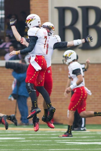 Oct 19, 2013; Winston-Salem, NC, USA; Maryland Terrapins quarterback Caleb Rowe (7) celebrates with a teammate after throwing a touchdown pass during the third quarter against the Wake Forest Demon Deacons at BB&T Field. Wake defeated Maryland 34-10. Mandatory Credit: Jeremy Brevard-USA TODAY Sports