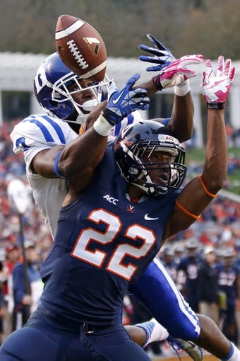 Oct 19, 2013; Charlottesville, VA, USA;  Duke Blue Devils wide receiver Jamison Crowder (3) and Virginia Cavaliers cornerback DreQuan Hoskey (22) battle for a pass in the third quarter at Scott Stadium. The Blue Devils won 35-22. Mandatory Credit: Geoff Burke-USA TODAY Sports