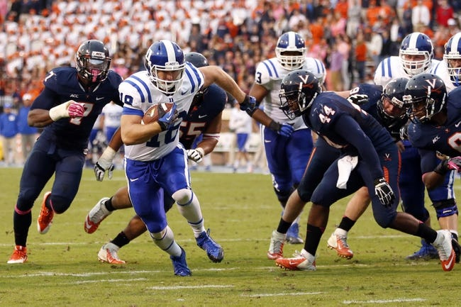 Oct 19, 2013; Charlottesville, VA, USA;  Duke Blue Devils quarterback Brandon Connette (18) runs with the ball to score a touchdown past Virginia Cavaliers linebacker Henry Coley (44) in the third quarter at Scott Stadium. The Blue Devils won 35-22. Mandatory Credit: Geoff Burke-USA TODAY Sports