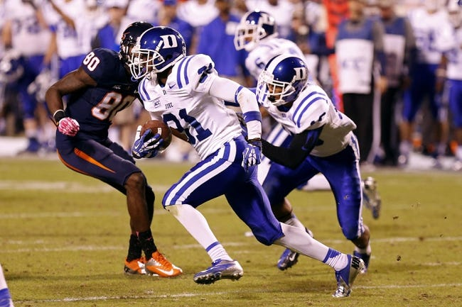 Oct 19, 2013; Charlottesville, VA, USA;  Duke Blue Devils cornerback Breon Borders (31) runs with the ball past Virginia Cavaliers wide receiver Adrian Gamble (80) after intercepting a pass in the fourth quarter at Scott Stadium. The Blue Devils won 35-22. Mandatory Credit: Geoff Burke-USA TODAY Sports