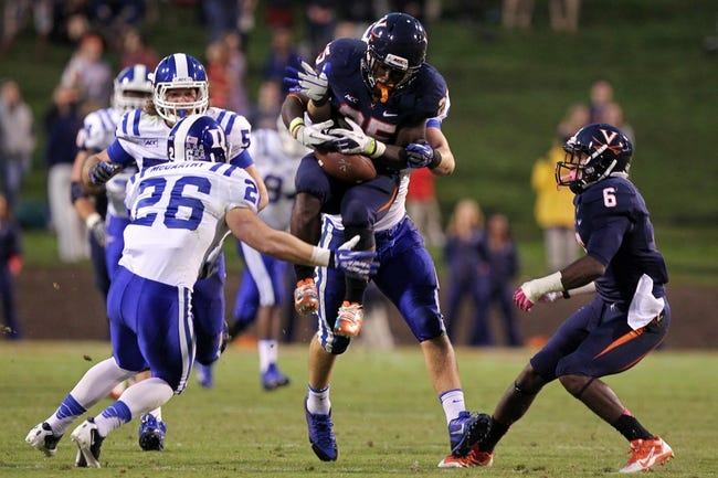 Oct 19, 2013; Charlottesville, VA, USA;  Virginia Cavaliers safety David Marrs (25) leaps to catch the ball as Duke Blue Devils safety Corbin McCarthy (26) defends in the fourth quarter at Scott Stadium. The Blue Devils won 35-22. Mandatory Credit: Geoff Burke-USA TODAY Sports