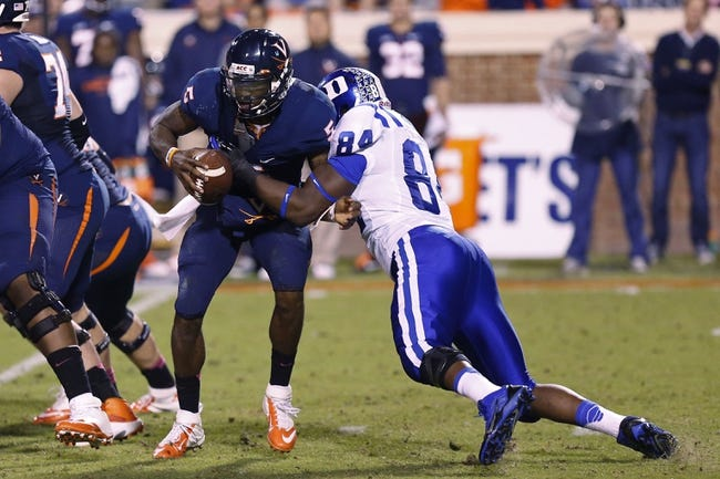 Oct 19, 2013; Charlottesville, VA, USA;  Virginia Cavaliers quarterback David Watford (5) is tackled by Duke Blue Devils defensive end Kenny Anunike (84) in the fourth quarter at Scott Stadium. The Blue Devils won 35-22. Mandatory Credit: Geoff Burke-USA TODAY Sports