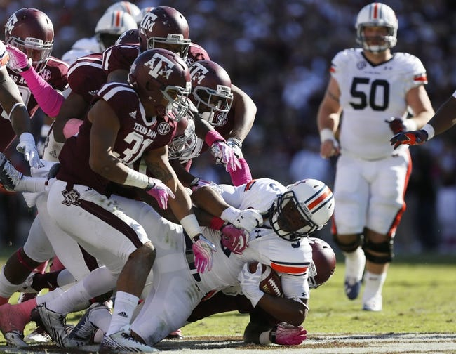 Oct 19, 2013; College Station, TX, USA; Auburn Tigers linebacker Jake Holland (5) is tackled by Texas A&M Aggies linebacker Darian Claiborne (behind) during the first half at Kyle Field. Mandatory Credit: Soobum Im-USA TODAY Sports